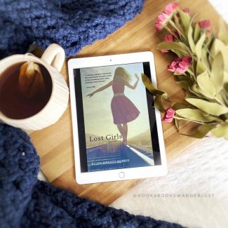 "The cover image for the book ""The Lost Girls"" by Ellen Birkett Morris, a girl in a dress walking one foot in front of the other down a solid white line on a road, is displayed on an iPad laying on a piece of wood surrounded by a cup of tea, a navy blue throw blanket, and some dark pink flowers."