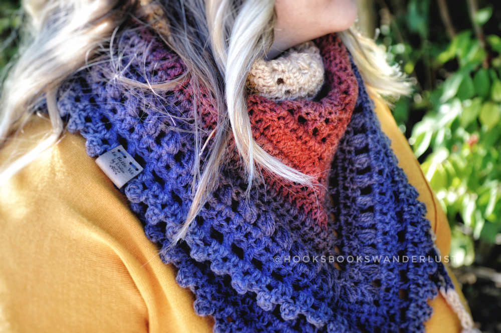 A close up of a blonde woman's autumn walks triangle scarf showing detail of the puffs, mesh, and picots.