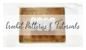 """4 skeins of yarn are arranged on a rustic drafting board with the words """"Crochet Patterns & Tutorials"""" in dark blue across an opaque white banner."""