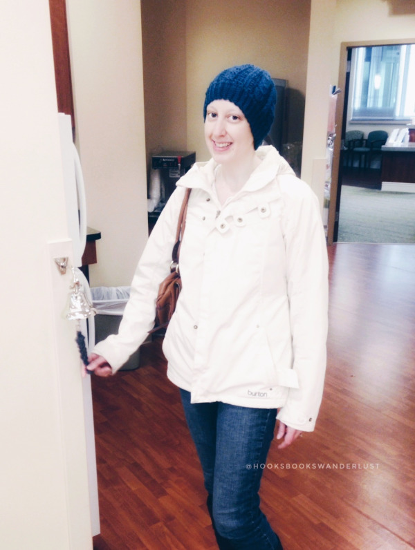 Kristen, dressed in a cream winter coat and wearing one of her blue crocheted hats poses as she rings the bell for her last chemo treatment.