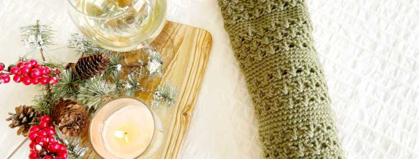 An olive wood cutting board holds a candle and a glass of white wine with some Christmas greenery dusted with snow and sprigs of red berries next to a bottle of wine encased in a crocheted wine sleeve in an olive green color.