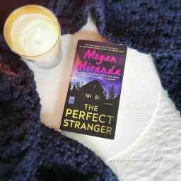 "A round white wood board with a navy blue blanket arranged around it has a lit candle burning on it and a copy of the paperback for the title ""The Perfect Stranger"" by Megan Miranda laying on it."