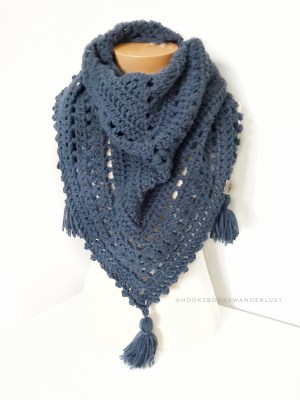 A mannequin sits on a white table in front of a light gray wall wearing a muted blue version of the Autumn Walks Scarf in a chunky yarn variation.