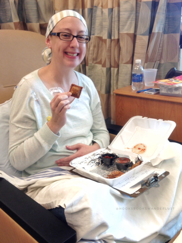Kristen sits in her treatment chair under a bevy of blankets eating a St Louis favorite, toasted raviolis.