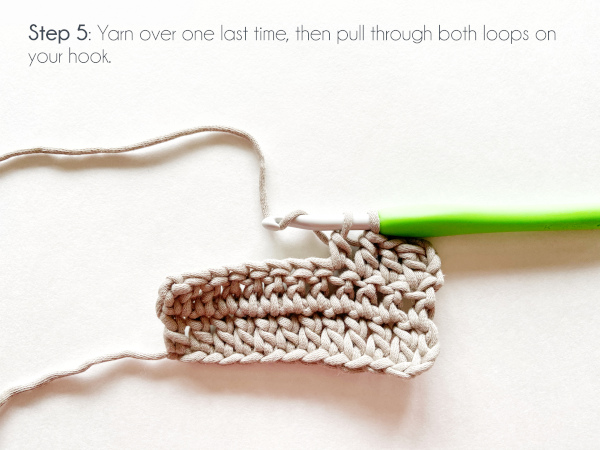"A swatch of double crochet in taupe color shows a half-formed double crochet with two working loops left on the loop and the working yarn wrapped over the hook again. Text on the photo reads: ""Step 5: Yarn over one last time, then pull through both loops on your hook."""