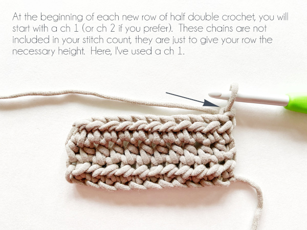 """""""At the beginning of each new row of half double crochet, you will start with a chain 1 (or chain 2 if you prefer). These chains are not included in your stitch count, they are just to give your row the necessary height. Here, I've used a chain 1."""" Photo shows a taupe swatch of 3 rows of half double crochet and a crochet hook having just completed one chain stitch at the beginning of the 4th row. A blue arrow points to the chain stitch."""