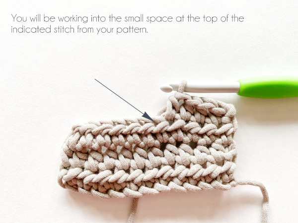 """""""You will be working into the small space at the top of the indicated stitch from your pattern."""" Photo shows a taupe swatch of 3 rows of half double crochet with 4 stitches in the 4th row worked by a green handled hook. A blue arrow points to the space where the next stitch will be worked."""
