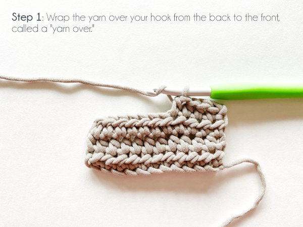 """""""Step 1: Wrap the yarn over your hook from the back to the front, called a 'yarn over.'"""" Photo shows a 4th row in progress, with 4 stitches worked and the yarn wrapped over the green handled crochet hook ready to work the next stitch."""
