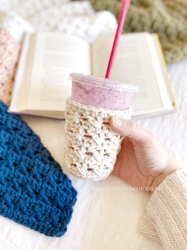 A woman's cream sweater covered arm and hand appear holding a purple smoothie held with a white XOXO Cold Cup Cozy in the foreground with the XOXO Throw, an open book and a white bedspread appear in the background.