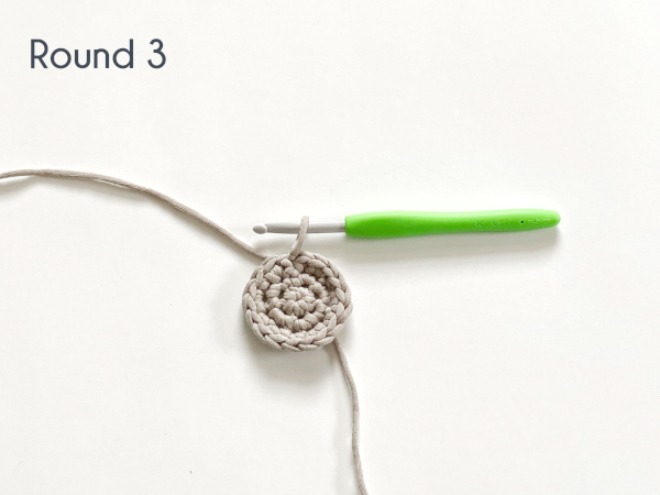"Three rounds of single crochet have been worked in a flat circle in a taupe colored cotton yarn laying on a white background. Text on the photo reads: ""Round 3."""