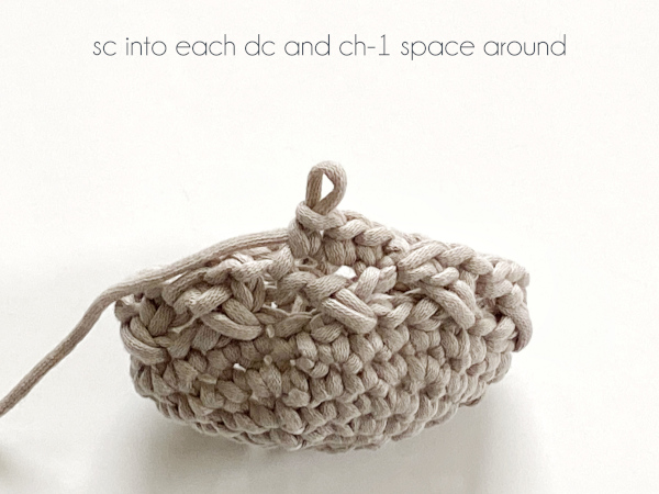 """A half-finished pattern shows seven rounds completed and the eighth round's first three stitches worked in a taupe yarn laying on a white background. Text on the photo reads: """"sc into each dc and ch-1 space around."""""""