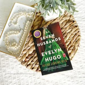 "A paperback copy of the book titled ""The Seven Husbands of Evelyn Hugo"" by Taylor Jenkins Reid rests on a weaved wicker tray with a matching set of pearl necklace and bracelets on a gilded white tray and a small plant, all of which lays on a white bedspread."