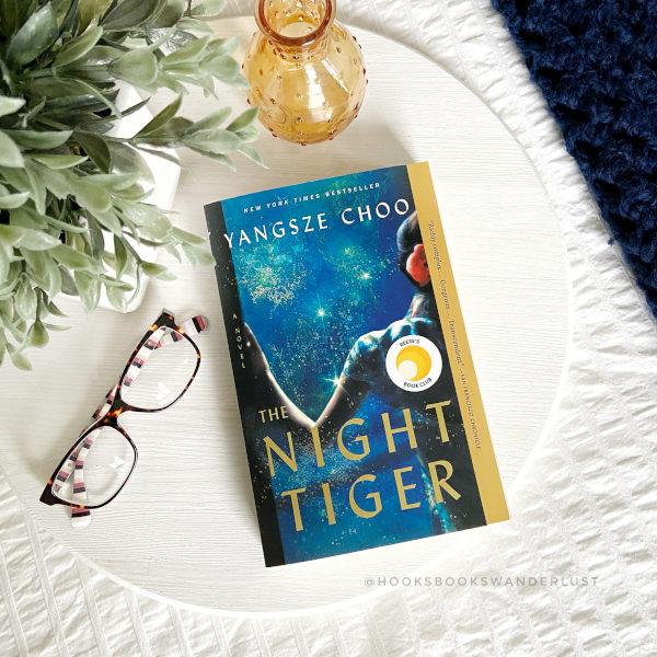 """A paperback copy of the book titled """"The Night Tiger"""" by Yangsze Choo rests next to a paid of glasses, a gold-colored glass vase and a small potted plant on a white tray laying on top of a white bedspread with a navy blue throw blanket off to the right."""