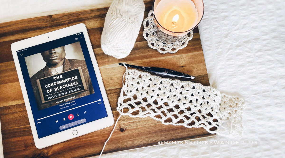 """An iPad showing the cover image of an audiobook titled """"The Condemnation of Blackness"""" by Khalil Gibran Muhammad lays next to a working crochet project, a ball of cream yarn, and a candle lay on a wooden board on top of a white bedspread."""