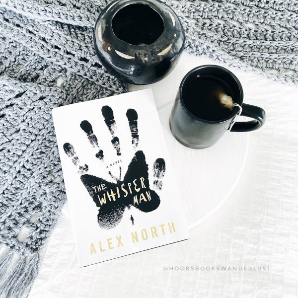 A hardback copy of The Whisper Man by Alex North lays on a white wooden circle next to a black mug of tea and a black ceramic vase with a gray pocket scarf arranged around it, all on top of a white bedspread.