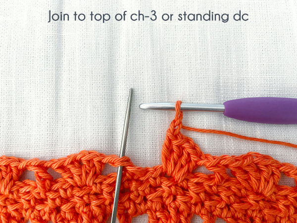"""""""Join to top of ch-3 or standing dc."""" A needle inserted through the top of the pictured standing double crochet marks where to join the round closed."""