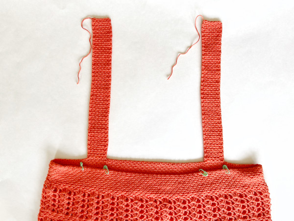 Image shows the back side of the garment and the completed but unattached straps with 4 stitch markers marking where the straps will be sewn to the back of the garment.