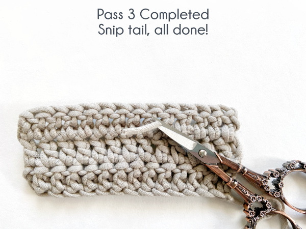 """Image shows a pair of embroidery scissors cutting the remaining yarn tail from the back of a swatch of double crochet. Text reads: """"Pass 3 Completed: Snip tail, all done!"""""""