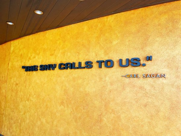 """A yellow curved wall under a wood plank ceiling with can lights has a quote from Carl Sagan: """"The sky calls to us."""""""