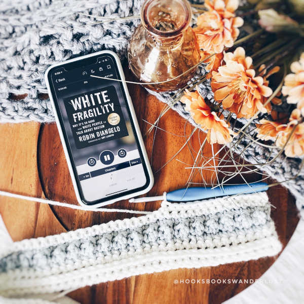 """An iPhone displaying the cover of an audiobook titled """"White Fragility: Why It's So Hard for White People to Talk About Racism"""" by Robin DiAngelo rests on a wood tray amidst a gray crocheted shawl, orange glass bud vase, orange flowers and a crochet project in progress."""