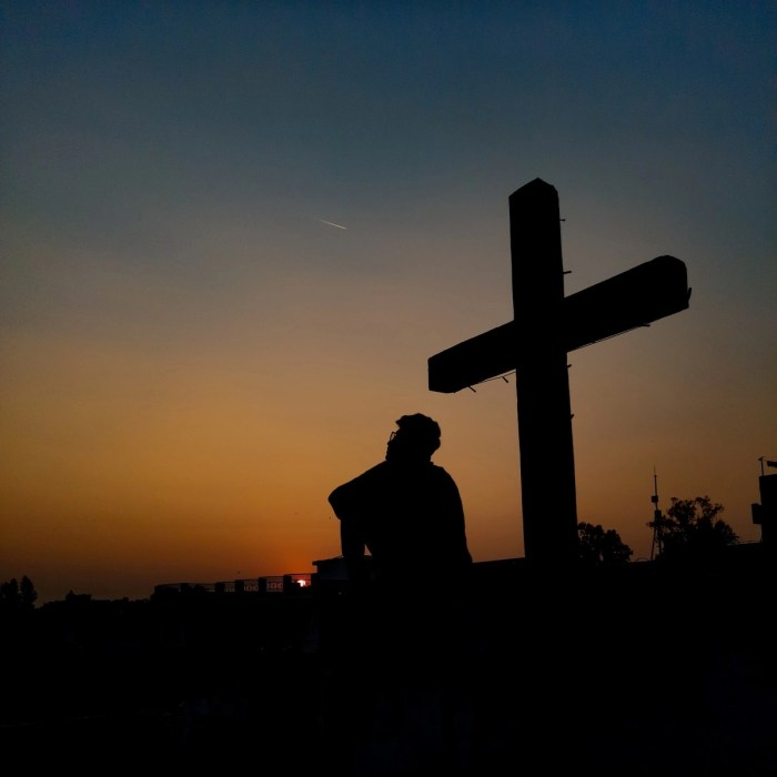 silhouette of man standing near cross during sunset