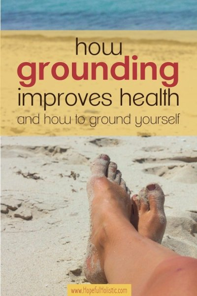 Image of bare feet in the sand at a beach with text overlay- how grounding improves health and how to ground yourself
