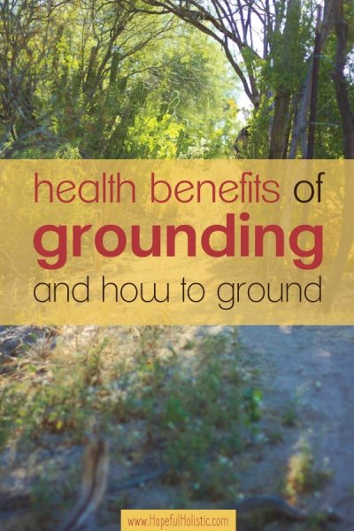 Background of ground and trees with sunlight and text overlay- health benefits of grounding and how to ground