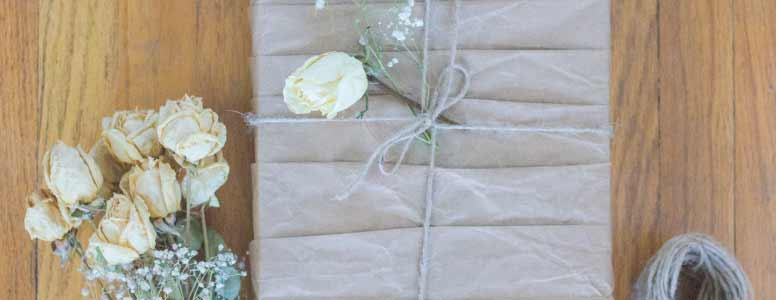 brown paper-wrapped present with twine and dried white roses