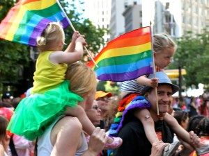 A family from our congregation waving rainbow flags at the Pride Parade