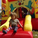 Bild Kind Frontal auf Mini-Hüpfburg Clown