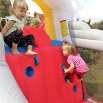 Zwei kleine Mädchen klettern auf Hüpfburg Formel 1 von Hopsi Hüpfburg Vermietung