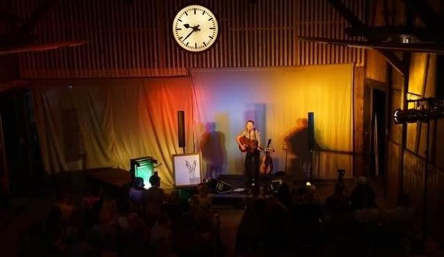 Mitten in der Güterhalle hängt eine alte Bahnhofsuhr – darunter spielt und singt ein überzeugender Ian Fisher. Foto: Roller