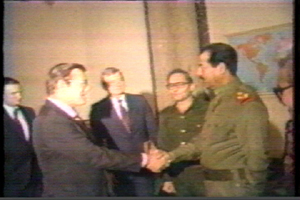 Hussein and Donald Rumsfeld shake hands