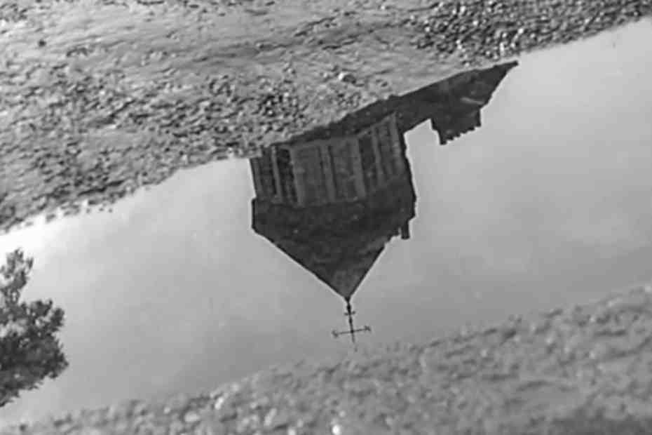reflection of a house in a puddle