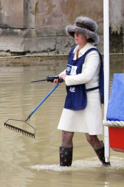The very well dressed Fence Judge Jane Knight tries to rake the water?