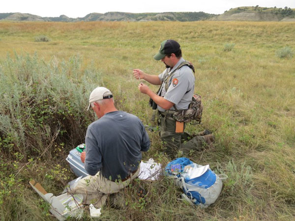 Colorado State University researcher Dan Baker, left, and Theodore Roosevelt National Park wildlife biologist Blake McCann prepare syringe darts to deliver a contraceptive vaccine.
