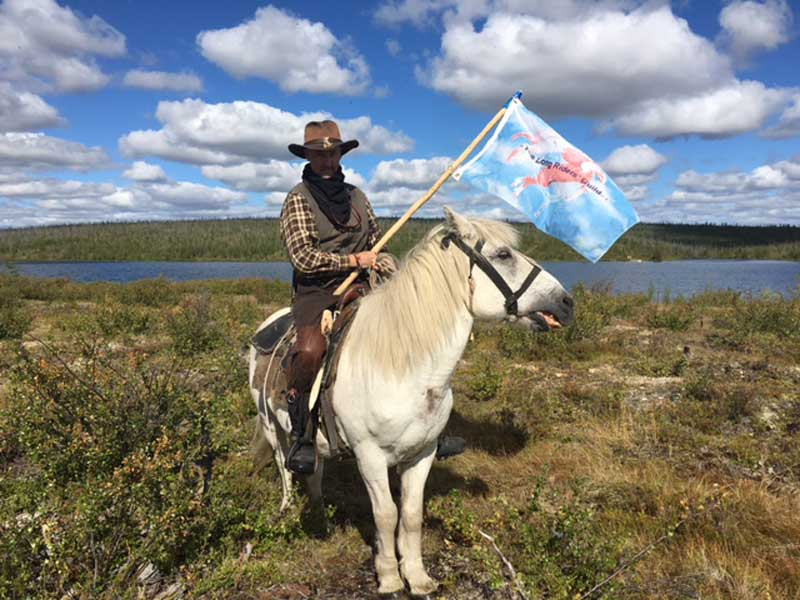 New Zealand Long Rider Ian Robinson sets off in Siberia in August, 2016. He is holding the flag of the Long Riders' Guild.