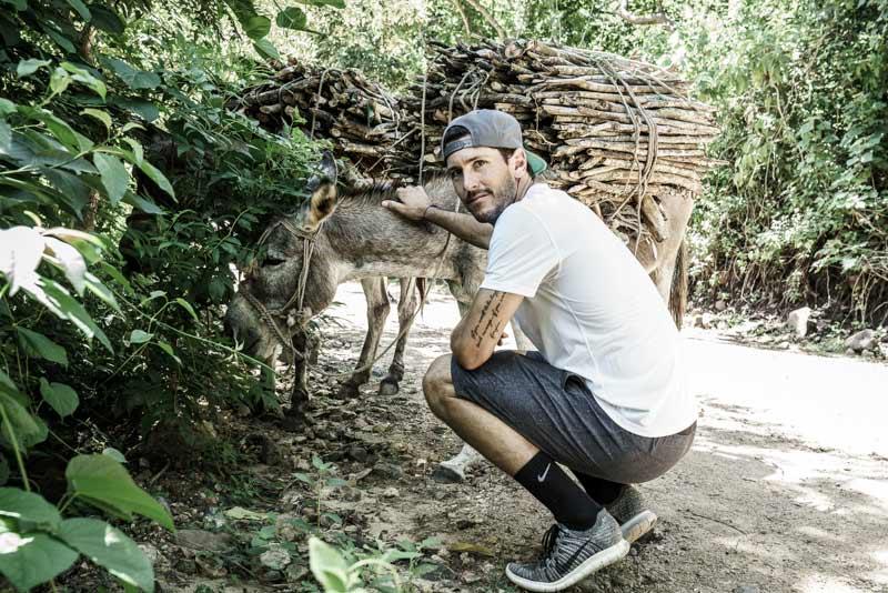 Nic Roldan and a working donkey in Guatemala. © Enrique Urdaneta