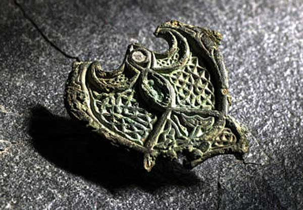A female Norwegian Viking who died during the 9th century was buried wearing a status symbol: this repurposed piece of bronze jewellery which was most likely originally created as a fitting on horse harness. Photo: Norwegian University of Science and Technology