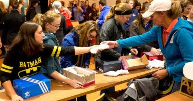 St. Andrews Western coach Carla Wennberg hands a student a pair of socks to include in a package.