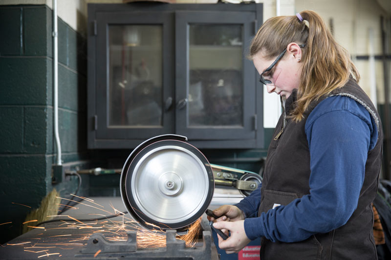 Kahlan Schramm crafting a horseshoe in the farrier shop.