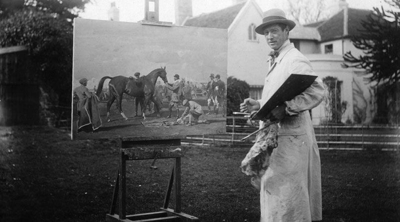 Sir Alfred Munnings photographed at work on a racing scene in 1925.
