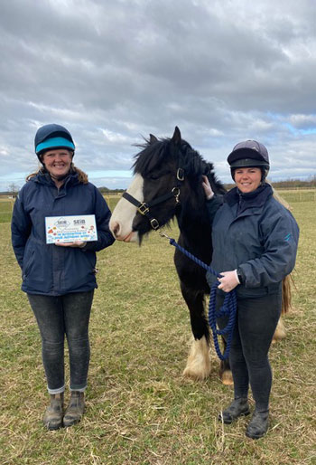 Bransby Horses staff members, Jess Hester, left, and Stef Leversedge with equine resident Miya and the charity's £15,000 cheque from the SEIB Giving Virtual Awards.
