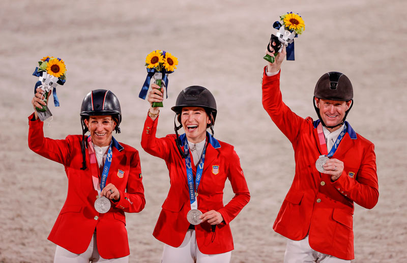 The US team of Laura Kraut (Baloutinue), Jessica Springsteen (Don Juan van de Donhoeve) and McLain Ward (Contagious) celebrate winning the silver medal in the team showjumping at Tokyo 2020.