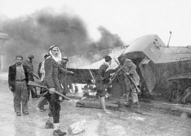 """לוחמים ערבים ליד משאית אספקה משוריינת של ה""""הגנה"""" כשהיא בוערת, בדרך לירושלים, - מלחמת העצמאות 1948"""