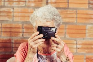 an old woman using a camera