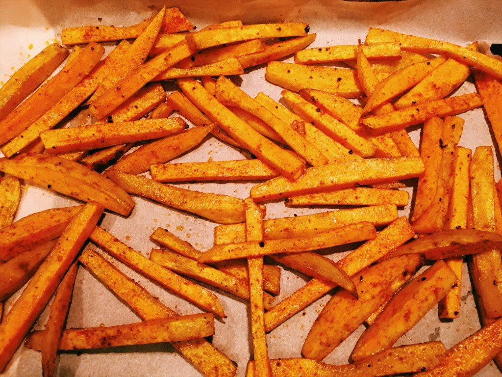 Place the sweet potato fries on a lined sheet tray and remove from oven to flip halfway through