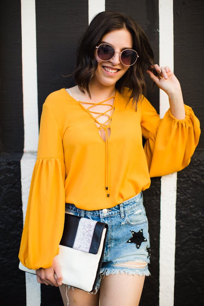 Round sunglasses Mustard yellow blouse Star Shorts