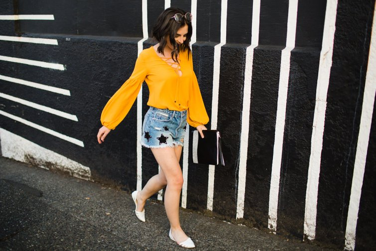 Star print denim distressed shorts and mustard lace up blouse