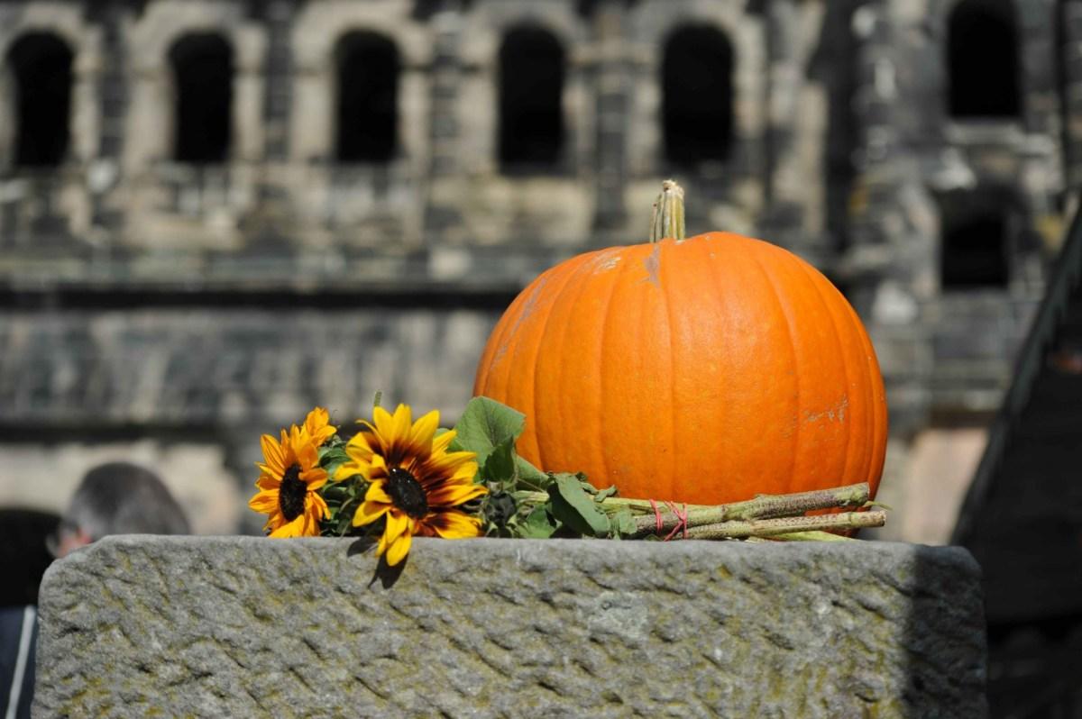 Ein Kürbis und ein Bund Sonnenblumen liegen vor der Porta Nigra